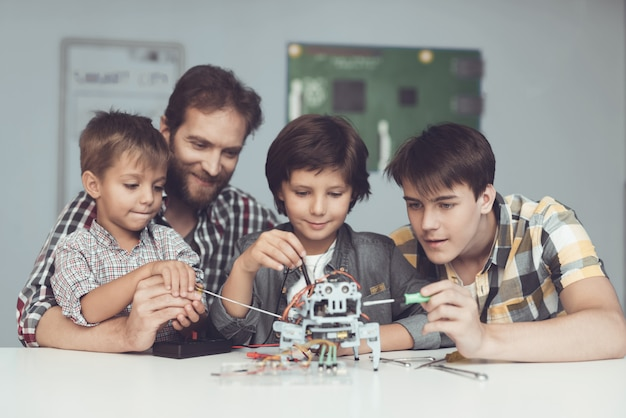 Two boys and male sit in the workshop and construct a robot.
