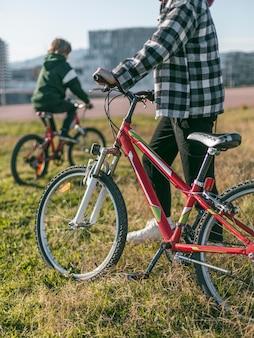 自転車を持って芝生の上にいる2人の男の子