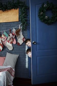 Два мальчика выглядывают из-за открытой двери в серой комнате новогоднего украшения.