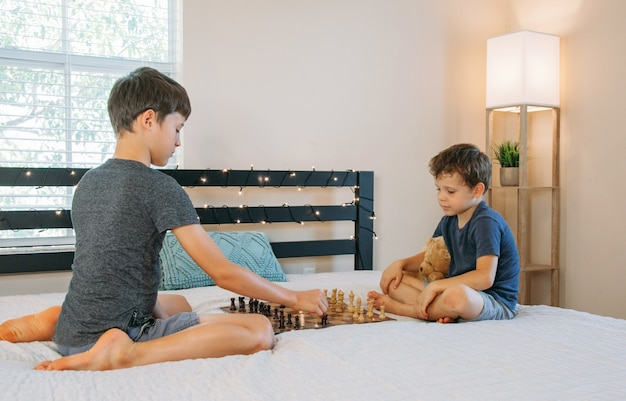 Two boys playing chess at home on the bed children practice playing a board game