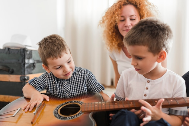 Two boys playing guitar in front of their mother