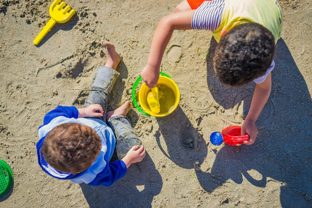 Two boys playing over sand with beach toys
