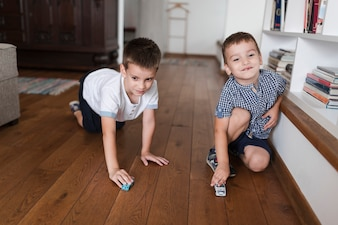 Two boys playing with car toys on hardwood floor