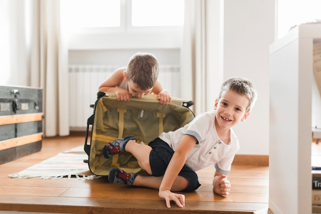 Two boys playing with luggage