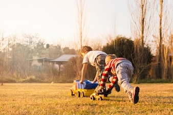 Two boys playing with toy vehicles on the green grass