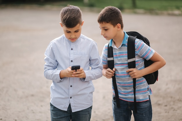 Two boys plays online games in quarantine. young boys smile and use phone. one look how play another