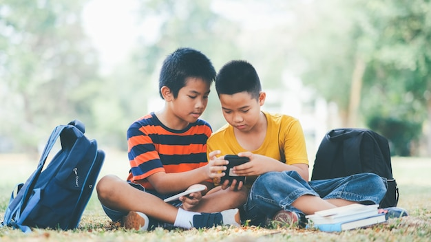 Two boys of primary using mobile phone together.