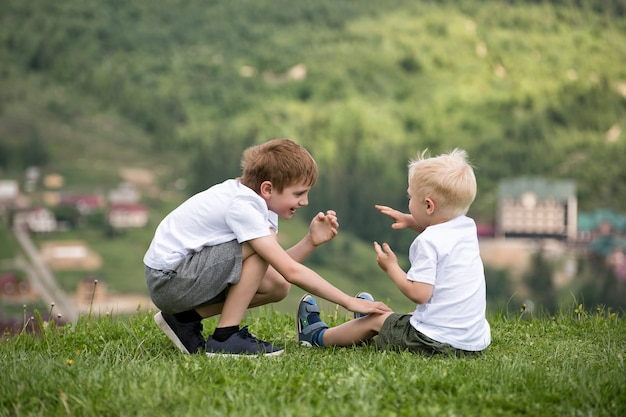 Two boys sit on a hill and have fun. back view