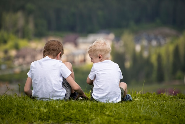 Two boys sit on a hill and have fun.