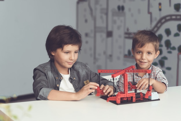 Two boys sit in a workshop and create a merry-go-round