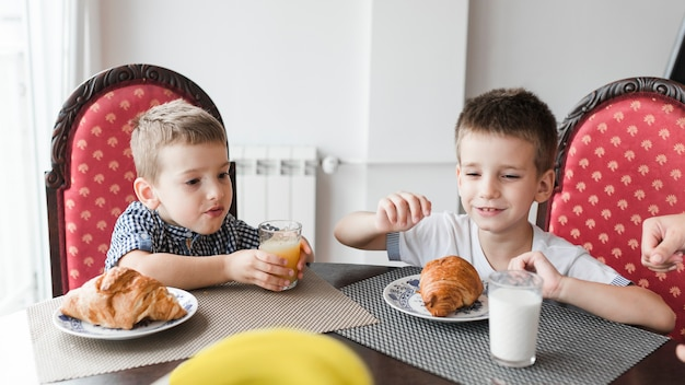 Two boys sitting on chair with glass of milk and croissants over desk