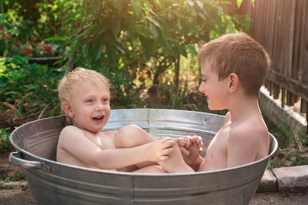 물과 놀이가 가득한 금속 분지에 앉아있는 두 소년