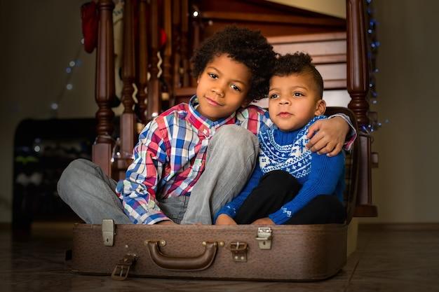 スーツケースの中に座っている2人の男の子。階段の横に座っている2人の兄弟。これは忘れられない瞬間です。いつも一緒に。