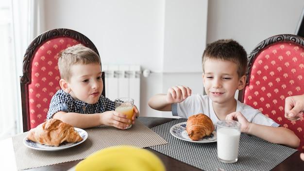机の上にミルクとクロワッサンのガラスを着た椅子に座っている2人の男の子