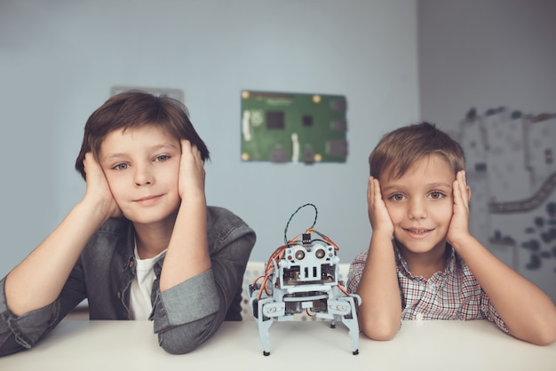 Two boys sitting at table and constructing robot.