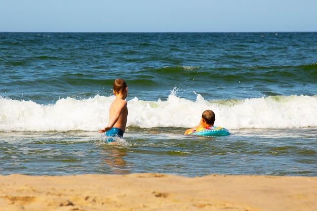 2人の男の子が水中で泳いでいます。海で遊んでいる二人の兄弟。波に飛び乗る。海で楽しい子供時代。熱帯での休暇。男の子たちは海で遊ぶ。