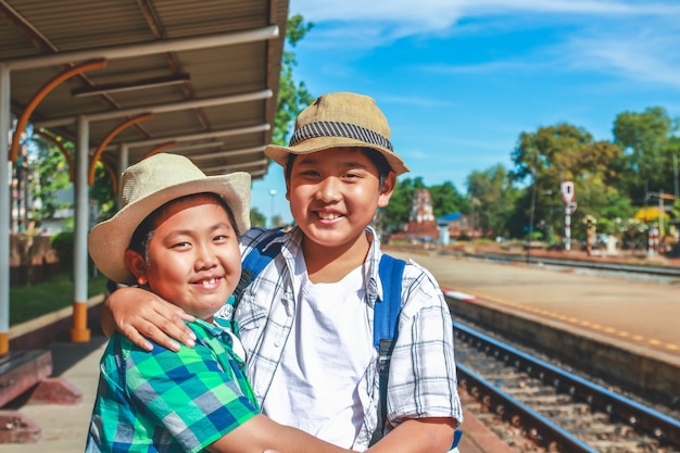 Two boys travel to stand and wait for the train at lopburi station, thailand.
