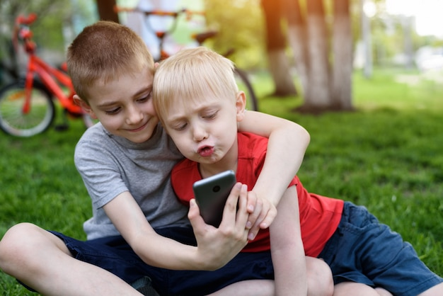 Two boys using a smartphone are sitting on the grass