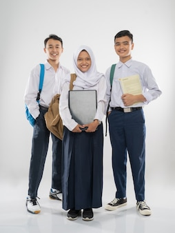 Two boys and a veiled girl in junior high school uniforms stand smiling carrying a laptop computer b...
