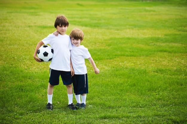 サッカーのフィールドでサッカーボールを持つ2人の男の子