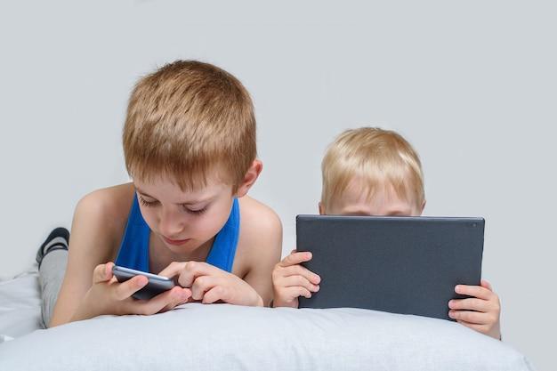 가제트가있는 두 소년이 침대에 누워 있습니다. 아이들은 스마트 폰과 태블릿을 사용