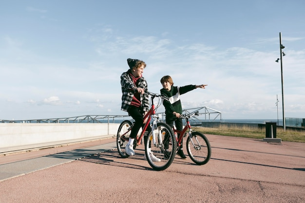 屋外で自転車を持っている2人の男の子
