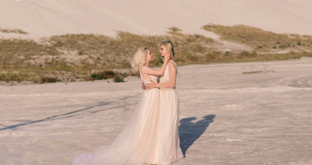 Two brides women in white dress with blonde hair hugging each other, lesbian wedding