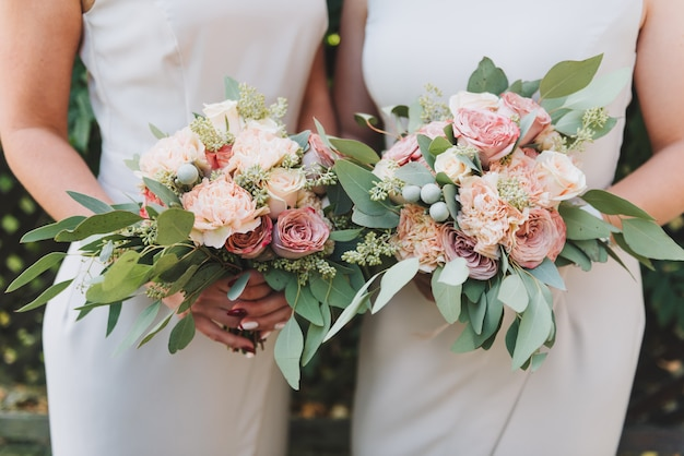 Two bridesmaids holding their bouquets with peonies and eucalyptus