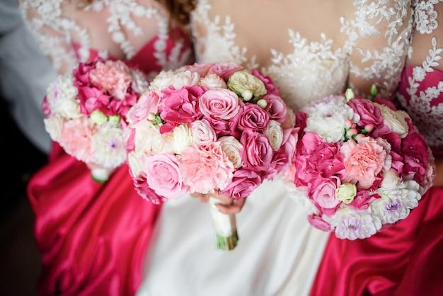 Две подружки невесты в розовых платьях и потрясающая блондинка невесты сидят на кровати