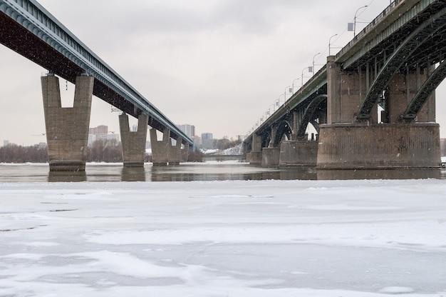 Два моста в городе через реку. зимний снежный день