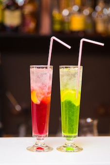 Two bright colorful cocktails in the bar