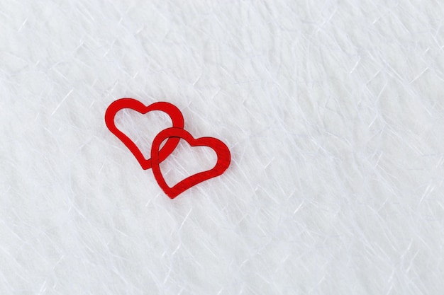 Two bright red hearts on a white blurred translucent fabric. greeting card, background or invitation with copy space for text. flat lay.