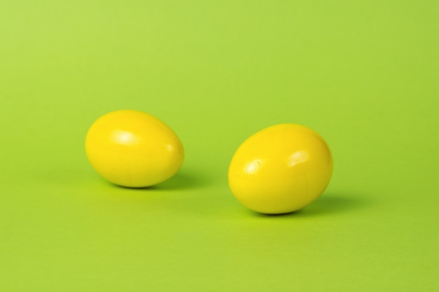Two bright yellow eggs on a green background.