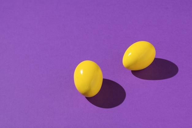 Two bright yellow eggs on a purple background.