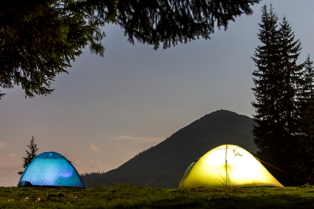 Two brightly lit tourist tents on green grassy forest clearing on dark mountain and clear blue starry sky copy space.