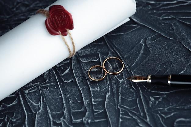 Two broken golden wedding rings divorce decree document. divorce and separation concept Premium Photo
