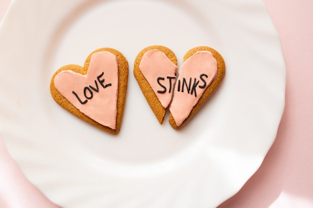 Two broken heart gingerbread cookies decorated with pink fondant with the message love stinks. heartbreak concept.