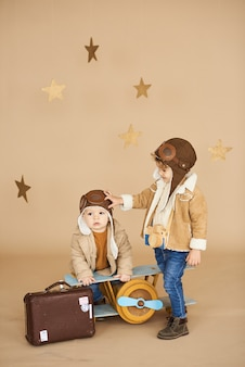 Two brothers are played with a toy airplane and a suitcase on a beige background