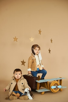 Two brothers are played with a toy airplane and a suitcase on a beige background.