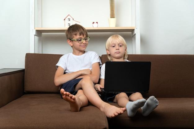 二人の兄弟がソファに座ってラップトップを見ています。手にラップトップを持つ子供。