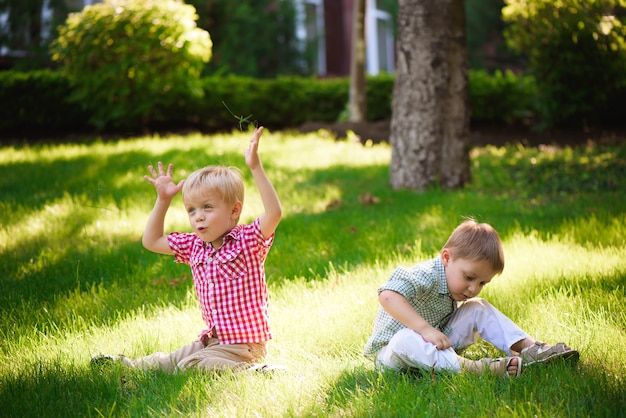 二人の兄弟が公園の日当たりの良い空き地に座って友達を待っています
