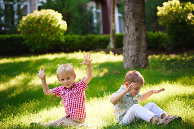 Two brothers are sitting on sunny glade in park and waiting for friends