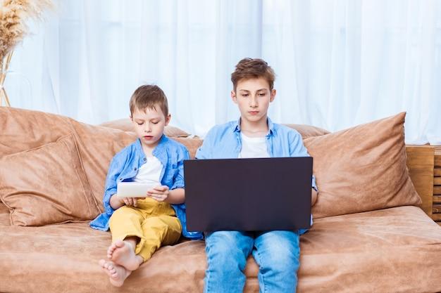 Два брата просматривают интернет на ноутбуке и планшете. современный образ жизни