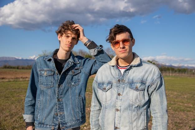 デニム ジャケットを着た 2 人の兄弟が野外の野原でポーズをとる、兄弟愛のコンセプト。