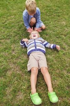 Два брата веселятся, играя на зеленой лужайке.