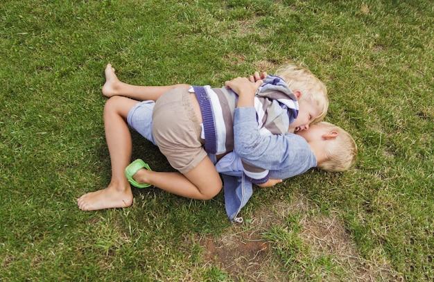 2人の兄弟は緑の芝生で遊んで楽しんでいます。