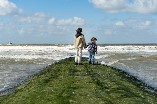 手をつないでいる2人の兄弟が北海の防波堤に滞在しています。週末をベルギーの海辺、クノックで過ごす少年たち。兄弟の友情。