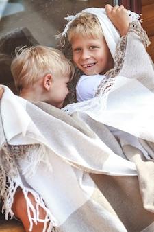 Два брата обнимаются и веселятся вместе под теплым уютным пледом.