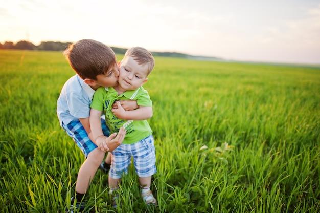緑の芝生のフィールドにいる2人の兄弟。