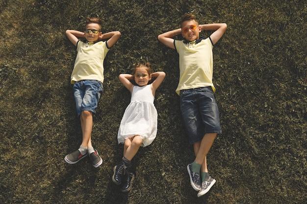 노란색 티셔츠를 입은 두 형제와 흰 드레스를 입은 여동생이 풀밭에 누워